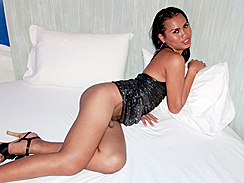 Shemale Ice Lying On Bed Leaning Against Pillow Wearing Grey Dress In High Heels Head Of Cock Poking Out Between Thighs