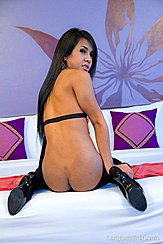 Asian Shemale Oil Sittig On Bed Looking Over Her Shoulder Baring Ass Wearing Black Heels