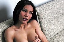 Asian shemale Jeje playing with cock on sofa