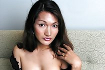 Asian shemale playing with cock on sofa