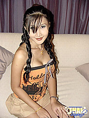 Pretty Postop Shemale Sitting On Bed Wearing Orange Top And Short Skirt