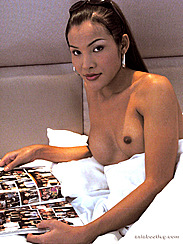 Ladyboy Reading Magazine In Bed Breasts Above White Sheets