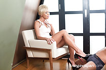 Sitting on chair painted fingernails giving footjob in high heels